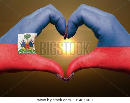 Heart And Love Gesture By Hands Colored In Haiti Flag During Beautiful Sunrise