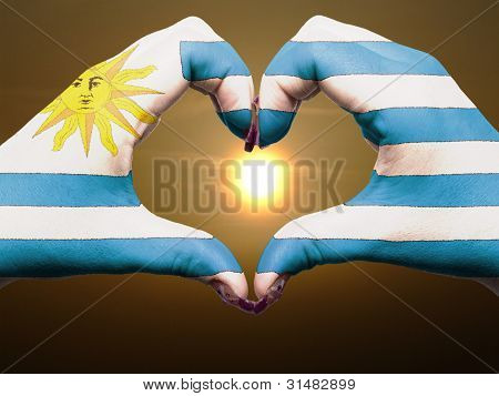 Heart And Love Gesture By Hands Colored In Uruguay Flag During Beautiful Sunrise For Tourism
