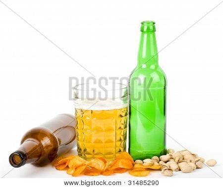 Beer green bottle and potato chips, pistachios isolated on a white