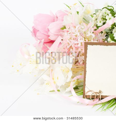 Gold wedding rings on a bouquet of white roses with banner add