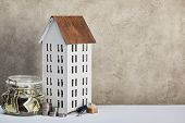 House Model, Moneybox With Dollar Banknotes, Keys And Silver Coins On White Table On Grey Background poster