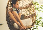 Beautiful Woman Relaxing At Home In Swing Chair. Woman Relaxing In Swing Chair At Home. Hipster Life poster