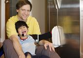 picture of physically handicapped  - Father on kitchen floor with disabled son cleaning the fridge - JPG