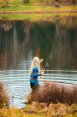 pic of fisherwomen  - beautiful blond girl fishing in pond at autumn - JPG