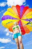 stock photo of parasailing  - Low angle view of a young woman in a bikini standing beneath a colourful inflated parasail canopy with a harness against cloudy blue sky in summer - JPG