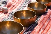 Indian Tibetan Bronze Healing Bowls Lie On A Sari In Perspective. Singing Healing Bowls Of Tibetan T poster