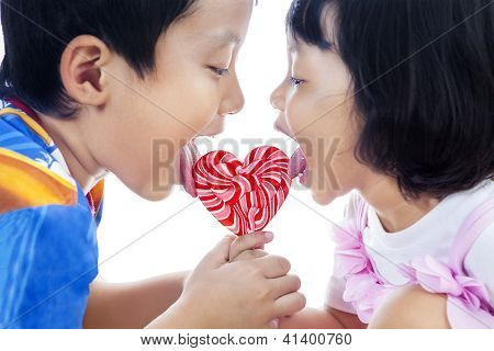 Cute Siblings Lick Lollipop