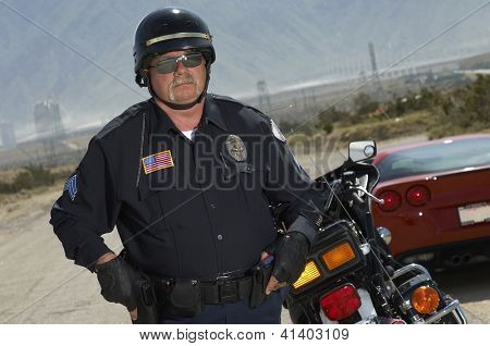 Police man on duty standing by bike