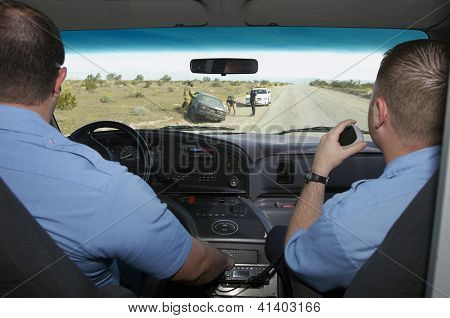 Paramedics looking through windshield at car crash scene