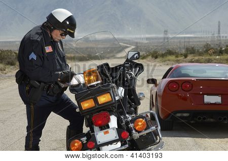 Police officer writing ticket by bike with car in the background