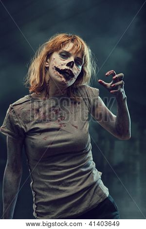 Creepy zombie with bloody hands over apocalyptic background