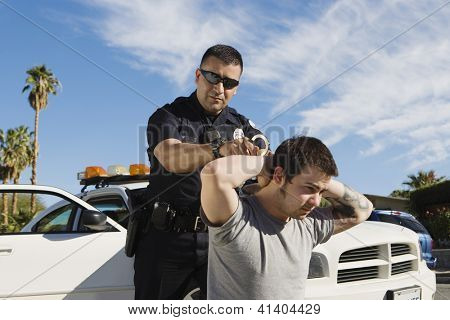 A mature police officer arresting young man