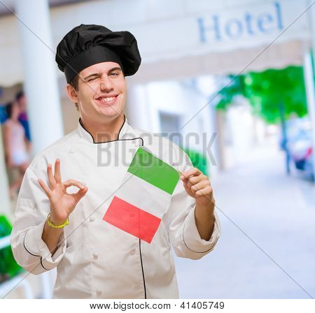Portrait Of A Young Chef Holding Italian Flag And Winking, outdoor