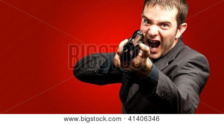 Angry Man Holding Gun against a red background