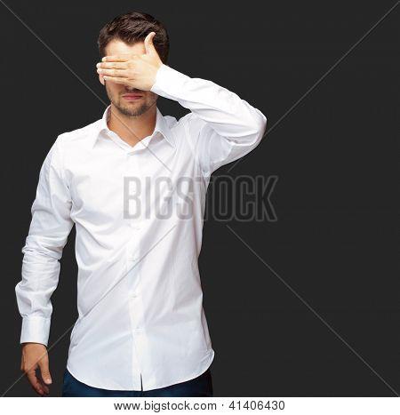 Retrato de um homem de negócios cobrindo os olhos isolados no fundo preto