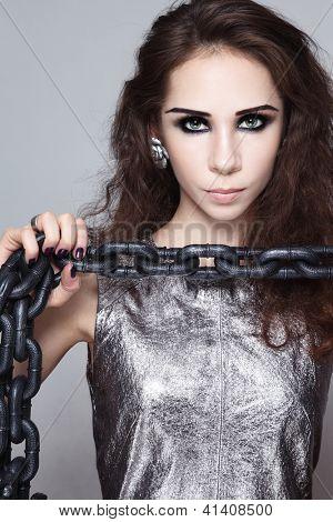 Retrato de jovem bonito com cadeia pesada em suas mãos