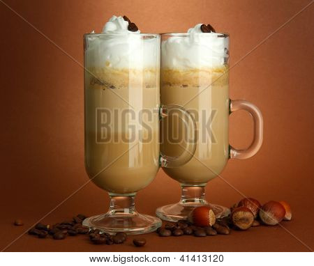 Fragrant coffee latte in glasses cups, on brown background
