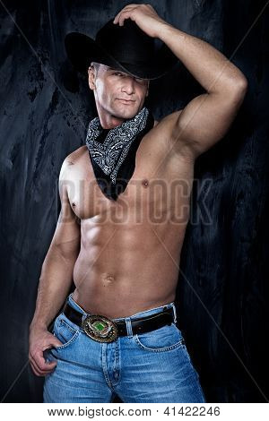 Muscular Handsome Man Posing In A Cowboy Hat And Jeans Over The Grunge Wall.