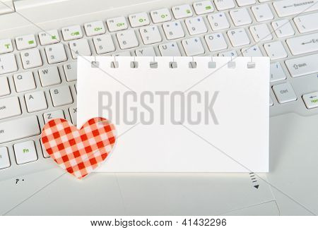 small red hearts and sticky note on Laptop keyboard