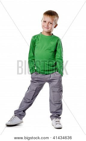 Portrait Of A Happy Little Young Boy Standing With Hands In Pocket Over White Background