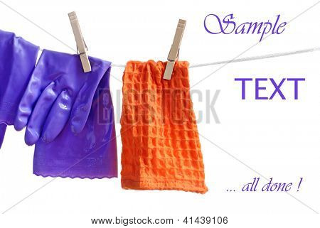 Wet household gloves and cleaning cloth hanging on clothesline to drip dry.  White background with copy space.  Concept - all done with spring cleaning!