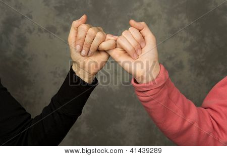 Closeup of mother and daughter holding pinkie fingers