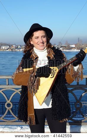 Lovely girl with balalaika is on embankment of Angara River in the city of Irkutsk