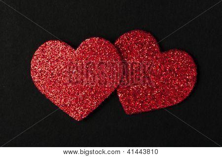 Corazones rojos brillantes sobre fondo negro