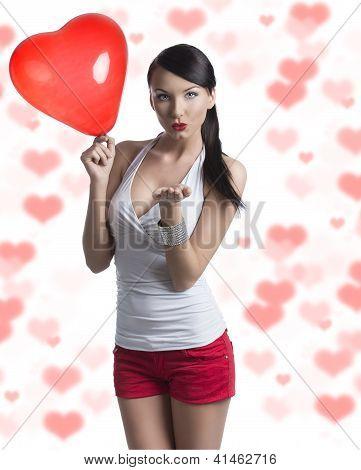 sexy Brünette mit herzförmigen Ballon sendet einen Kuss