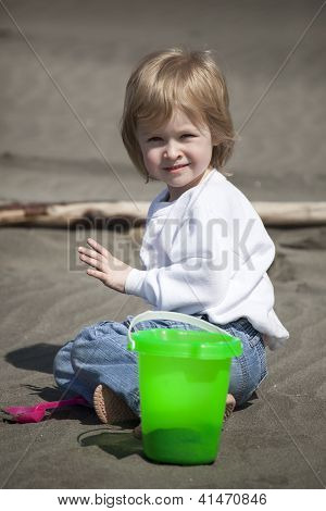 Cute Blonde Child Playing At The Beach