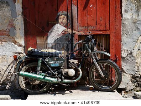 PENANG, MALAYSIA-DEC.9: Street Mural entitled 'Boy on a bike' painted  by Ernest Zacharevic in Penang on Dec.9, 2012. It was painted in conjunction with the 2012 George Town Festival.