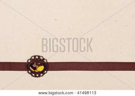 Brown Ribbon With Broche Over Vintage Gift Old Paper Background
