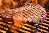 pic of rib eye steak  - Bone in rib eye steak on a grill with flames - JPG