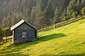 stock photo of outhouses  - Landscape with outhouse with small window on the hill - JPG