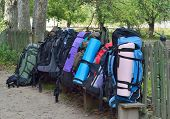 pic of knapsack  - Several big tourist knapsacks are collected on the bench by the fence - JPG