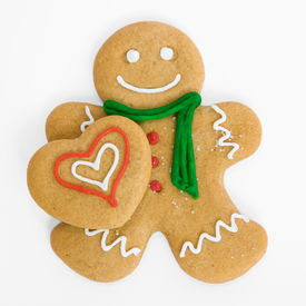 picture of gingerbread man  - Smiling gingerbread man holds iced gingerbread heart - JPG