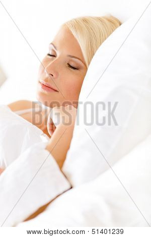 Close up view of sleepy woman in bed lying on the white cushion