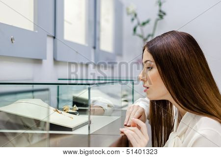 Close up view of girl looking at jewelry in window case at jeweler's shop. Concept of wealth and luxurious life