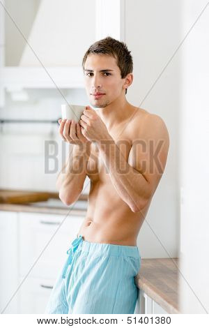 Half-naked man keeping cup of coffee stands at kitchen leaning on the fridge
