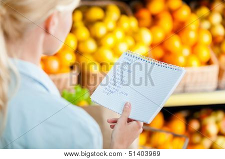 Girl looks through shopping list near the heap of fruits lying in the braided baskets in the shop