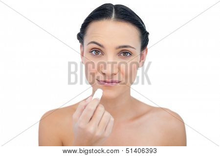 Curious natural model using lip balm on white background