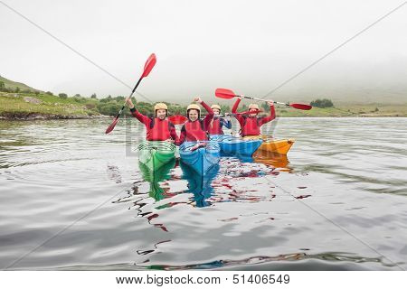 Fit friends rowing on a lake in kayaks and cheering at camera