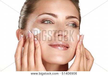 Beautiful Model Applying Cosmetic Cream Treatmen On Her Face