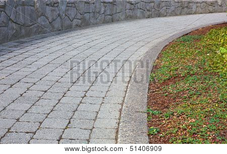 Curved stone path with stone wall