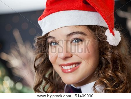 Closeup portrait of beautiful young woman wearing Santa hat in Christmas store