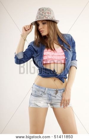 Young pretty woman with beautiful blond hairs and multicolor makeup and blue jeans dress short and shirt in the hat isolated on white background
