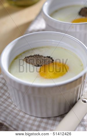 Baked egg with sliced truffle in a ramekin