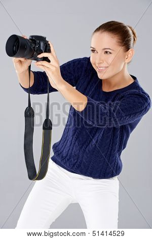 Pretty vivacious young female phoptographer smiling as she looks into the viewfinder on the back of her dslr camera  isolated on grey