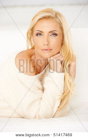 Beautiful dreamy woman with long blond hair wearing an elegant cream sweater lying on a sofa looking at the camera with a faraway expression