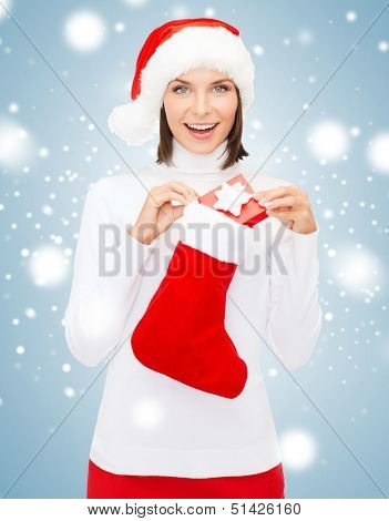 christmas, x-mas, winter, happiness concept - smiling woman in santa helper hat with small gift box and stocking